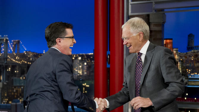 """In this photo provided by CBS, Comedy Central's Stephen Colbert, left, shakes hands with host David Letterman on the set of the """"Late Show with David Letterman,"""" Tuesday, April 22, 2014, in New York. The late-night transition from David Letterman to Steven Colbert and from Craig Ferguson to a yet-to-be-named host remains undecided, CBS Entertainment chief Nina Tassler said Thursday, July 17, 2014.Network meetings will be held in August to discuss the scheduling of Colbert's 2015 debut as """"Late Show"""" host, Tassler told a Television Critics Association meeting. (AP Photo/Jeffrey R. Staab) MANDATORY CREDIT, NO SALES, NO ARCHIVE, FOR NORTH AMERICAN USE ONLY"""