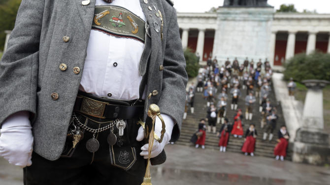 Bavarian riflemen and women in traditional costumes await to fire their muzzle loaders in Munich, southern Germany, Sunday, Oct. 7, 2012. Members of various shooting clubs of the region met for a salute on the last day of the famous Oktoberfest beer festival. (AP Photo/Matthias Schrader)