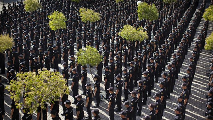 Police cadets attend a graduation ceremony in Madrid, Spain, Tuesday, July 17, 2012. Riot police cordoned off the entrance to a sprawling police facility to prevent demonstrating police officers from disrupting a graduation ceremony for some 1,200 cadets about to enter the police force. The demonstrators were protesting parts of the austerity package, namely the elimination of one of 14 paychecks that most Spanish civil servants get each year. The one being axed comes right before Christmas.  (AP Photo/Emilio Morenatti)