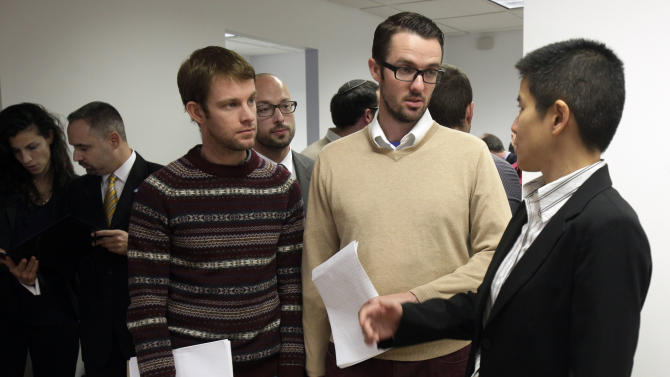 """Christine Sun, right, deputy legal director for the Southern Poverty Law Center, confers with Michael Ferguson, second right, and his partner Seth Anderson, before a news conference, in New York, Tuesday, Nov. 27, 2012. Ferguson, of Salt Lake City, is one of four gay men accusing a New Jersey organization of selling """"conversion therapy"""" services promising to make them straight. Instead, they told the news conference that they were subjected to humiliations, including having to strip naked, or taking a baseball bat to effigies of their mothers.  Sam Wolfe, staff attorney for the SPLC is at background center. (AP Photo/Richard Drew)"""