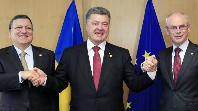 "Ukraine's President Petro Poroshenko, center, poses with European Commission President Jose Manuel Barroso, left, and European Council President Herman Van Rompuy, right, during an EU Summit in Brussels on Friday, June 27, 2014. Ukrainian President Petro Poroshenko has signed up to a trade and economic pact with the European Union, saying it may be the ""most important day"" for his country since it became independent from the Soviet Union. (AP Photo)"