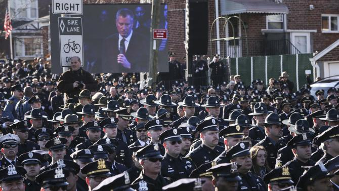 Law enforcement officers turn their backs on a live video monitor showing New York City Mayor Bill de Blasio has he speaks at the funeral of slain New York Police Department (NYPD) officer Rafael Ramos in New York