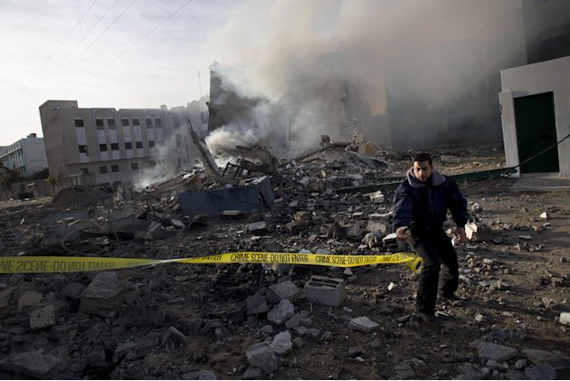 A Palestinian Hamas officer secures the area after an early morning Israeli airstrike on a building that served as a branch of the Interior Ministry in Gaza City, Friday, Nov. 16, 2012. Israel offered