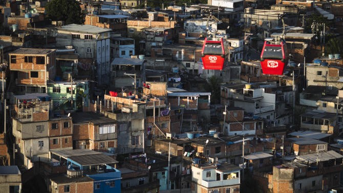 In this May 10, 2013 photo, cable-cars transporting commuters move over the Complexo do Alemao complex of shantytowns in Rio de Janeiro, Brazil.  The cable-car system linking six of its hilltops over a 3.5-kilometer (2.3-mile) route has become a popular tourist attraction. (AP Photo/Felipe Dana)