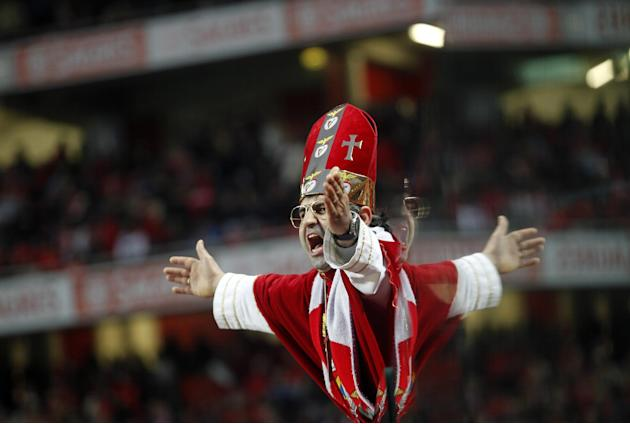 A Benfica supporter, reflected in a security glass, cheers prior the Portuguese league soccer match between Benfica and Sporting at Benfica's Luz stadium, in Lisbon, Sunday, Feb. 9, 2014. Strong w