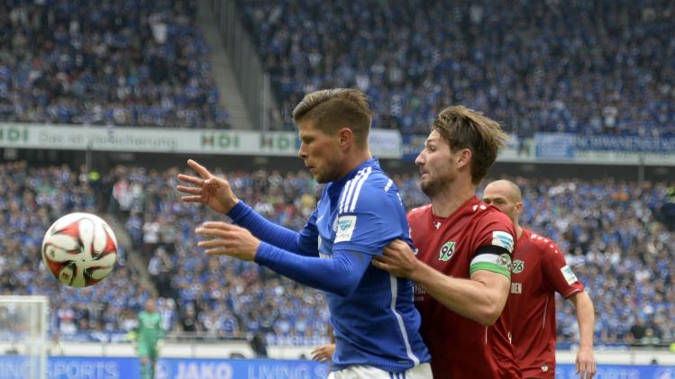 Hanover 96's Schulz and Schalke 04's Huntelaar fight for the ball during their German Bundesliga first division soccer match in Hanover