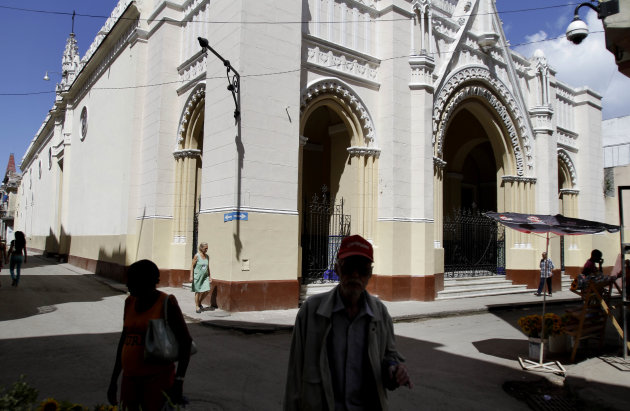 Pedestrians walk near the Virgin of Charity of Cobre Catholic church where thirteen Cuban dissidents have holed up to press for a meeting with Pope Benedict XVI when he visits, in Havana, Cuba, Wednesday March 14, 2012. Benedict's visit is scheduled for March 26-28. (AP Photo/Franklin Reyes)