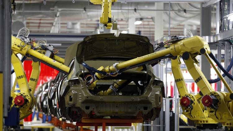 Robotic arms apply sealant to the interior of the frame of a 2015 Chrysler 200 vehicle at the Sterling Heights Assembly Plant in Michigan