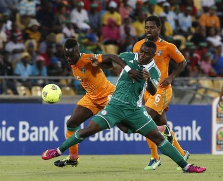 Ivory Coast's Tiote tackles Nigeria's Emenike during their African Nations Cup (AFCON 2013) quarter final soccer match in Rustenburg