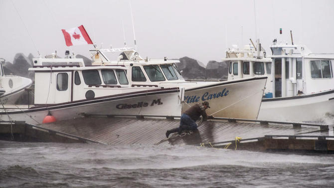 A lobster fisherman slips but holds on while trying to secure lines to his fishing boat after the floating dock broke apart during tropical storm Arthur in Escuminac, New Brunswick, on Saturday, July 5, 2014. Arthur hit Canada's Maritime provinces with near-hurricane strength winds and torrential rains, knocking out power to nearly 200,000 customers. (AP Photo//The Canadian Press, Diane Doiron)