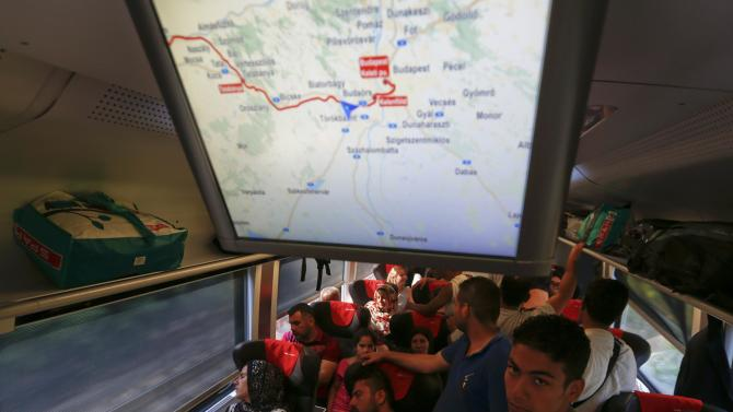 Travellers sit in a train with migrants on board, en route from Budapest to Vienna