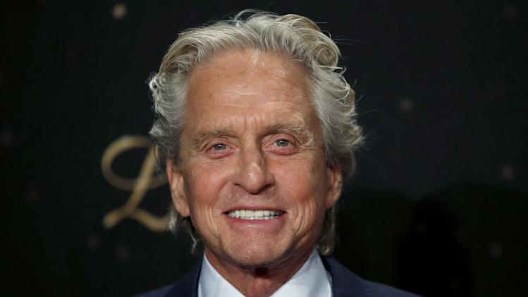 US actor Michael Douglas smiles as he arrives for the Germany premiere of the movie 'Behind The Candelabra' in Berlin, Germany, Monday, Sept. 2, 2013. (AP Photo/Michael Sohn)