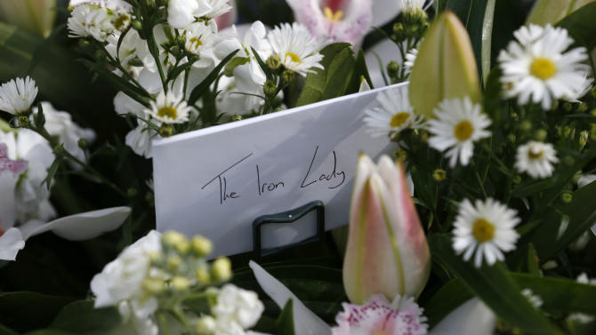 Floral tributes are seen being left outside the house of former British Prime Minister Margaret Thatcher who died from a stroke at age 87, in London, Monday, April 8, 2013. (AP Photo/Sang Tan)