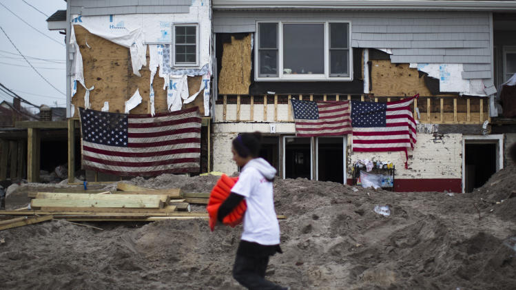 A volunteer passes a damaged home emblazoned with U.S. flags in the Rockaways, Saturday, Nov. 10, 2012, in the Queens borough of New York. Despite power returning to many neighborhoods in the metropolitan area after Superstorm Sandy crashed into the Eastern Seaboard, many residents of the Rockaways continue to live without power and heat due to damage caused by Sandy. (AP Photo/John Minchillo)