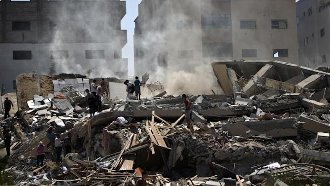 Palestinians on August 24, 2014 look through the rubble of a 12-storey apartment building that was hit by an Israeli air strike in Gaza City the day before
