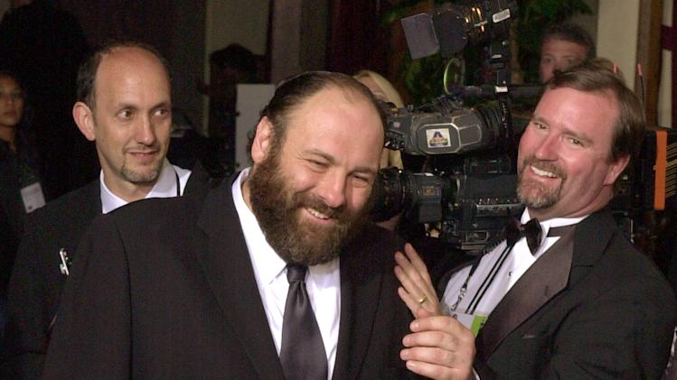 "FILE - In this March 9, 2003 file photo, James Gandolfini, center, is congratulated by others as he enters a backstage area saying ""Who called me rabbi?'"" after winning the award for outstanding performance in a lead role for the drama series ""The Sopranos"" at the 9th annual Screen Actors Guild awards in Los Angeles. Gandolfini, whose portrayal of a brutal, emotionally delicate mob boss in HBO's ""The Sopranos"" helped create one of TV's greatest drama series and turned the mobster stereotype on its head, died Wednesday, June 19, 2013 in Italy. He was 51. (AP Photo/Reed Saxon, File)"