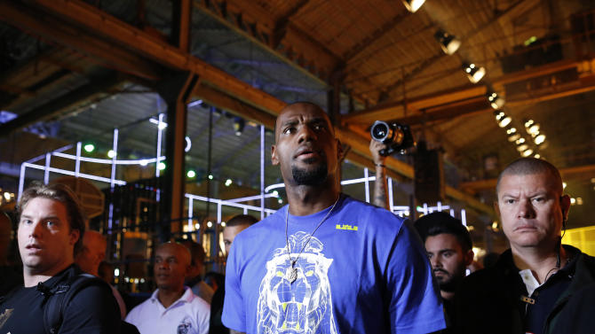 NBA basketball star LeBron James walks surrounded by security guards as he attends a promotional event at Phenom House, in Rio de Janeiro, Brazil, Saturday, July 12, 2014. James who will attend the final game of the 2014 soccer World Cup, has announced his return to play for the Cleveland Cavaliers after four years in Miami. (AP Photo/Leo Correa)