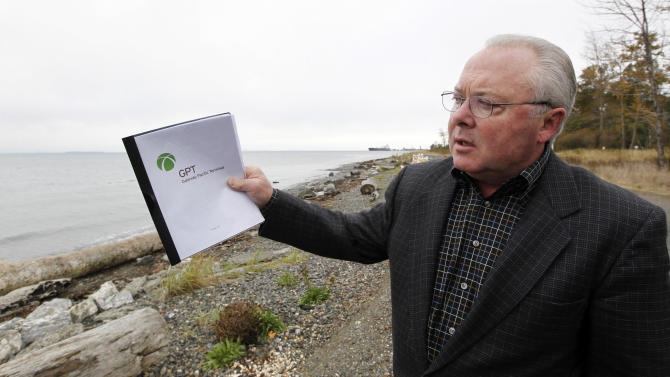 In this photo taken Oct. 23, 2012, SSA Marine spokesman Craig Cole talks about the proposed coal exporting terminal the company hopes to build on the beach behind him along the Strait of Georgia, in Ferndale, Wash., just north of Bellingham, Wash. The progressive college town of Bellingham is at the center of one of the fiercest environmental debates in the region: should the Northwest become a hub for exporting U.S. coal to Asia? A proposal to build one of as many as five coal terminals here has divided the town, pitting union and businesses that welcome jobs against environmentalists who worry about coal dust and greenhouse gas emissions. A trade group is running TV ads touting the projects, while numerous cities such as Seattle and Portland are opposing coal trains through their communities. (AP Photo/Elaine Thompson)