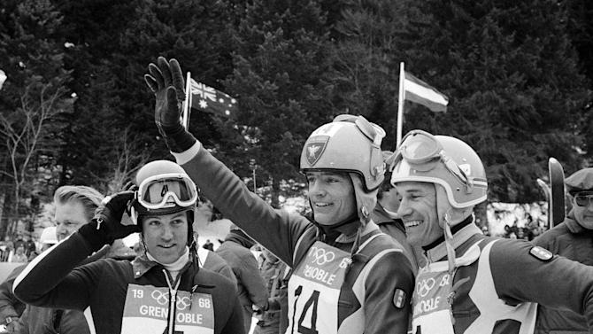 FILE - In this Feb. 10, 1968 file photo, Jean-Claude Killy, of France, center, waves after winning the gold medal in the men's downhill race at the Winter Olympic Games in Chamrousse, France. Guy Perillat of France, right, won the silver medal and  Jean-Daniel Datwyler of Switzerland, left, won the bronze medal. Ted Ligety became the first man in 45 years to win three gold medals at a skiing world championships by blowing away the field in winning his favored giant slalom on Friday, Feb. 15, 2013 in Schladming, Austria. The American can match French great Jean-Claude Killy, who earned four golds in 1968, if he wins Sunday's slalom. (AP Photo/File)