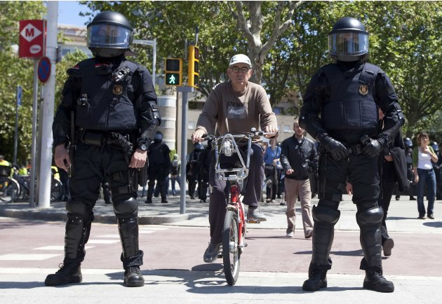 A man rides his bicycle between policemen in riot gear who are guarding the venue of a meeting of the ECB in Barcelona