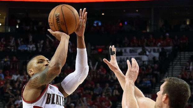 Portland Trail Blazers' Damian Lillard (L) shoots past Memphis Grizzlies's Beno Udrih in Game Four of the Western Conference quarterfinals during the NBA Playoffs at Moda Center on April 27, 2015