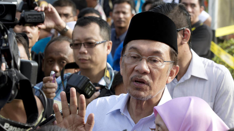 Malaysian opposition leader Anwar Ibrahim and his wife Wan Azizah talk to the media after voting at a polling station at Penanti in Penang state in northern Malaysia, Sunday, May 5, 2013. Malaysians have begun voting in emotionally charged national elections that could see the long-ruling coalition ousted after nearly 56 years in power.   (AP Photo/Mark Baker)