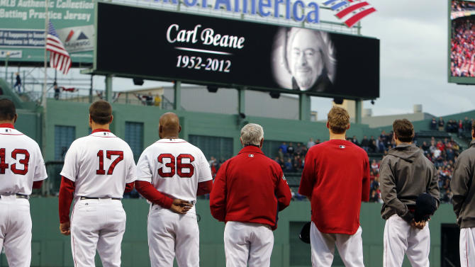 Boston Red Sox players and coaches line up in tribute to public address announcer Carl Beane during a memorial ceremony before a baseball game against the Cleveland Indians in Boston, Thursday, May 10, 2012. Beane died Wednesday after having a heart attack while driving. (AP Photo/Michael Dwyer)