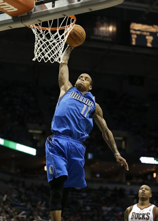 Dallas Mavericks' Monta Ellis (11) dunks in front of Milwaukee Bucks' Caron Butler during the first half of an NBA basketball game Saturday, Nov. 9, 2013, in Milwaukee