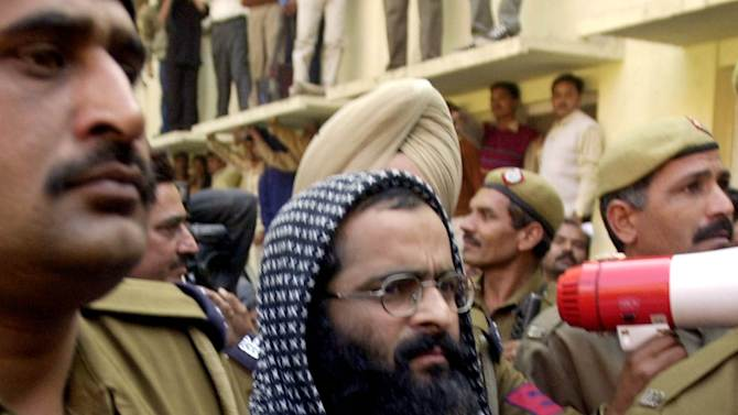 FILE – In this Dec. 16, 2002 file photo, Kashmiri man accused in the parliament attack Mohammed Afzal Guru, second right, is produced at a court in New Delhi, India. Afzal, convicted in the 2001 attack on India's Parliament, has been hanged in an Indian prison, a senior Indian Home Ministry official said Saturday, Feb. 9, 2013. The deadly Islamic militant attack killed 14 people, including the five attackers in 2001. (AP Photo/Aman Sharma, File)