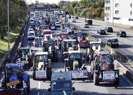French farmers converge on Paris, driving their tractors on the motorway
