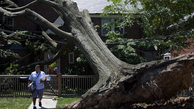 Giovanny Alvarez, a letter carrier for the U.S. Postal Service, leaves after delivering mail to a residence in Washington, Monday, July 2, 2012,  damaged by the powerful storm that swept through the region Friday.  (AP Photo/Evan Vucci)