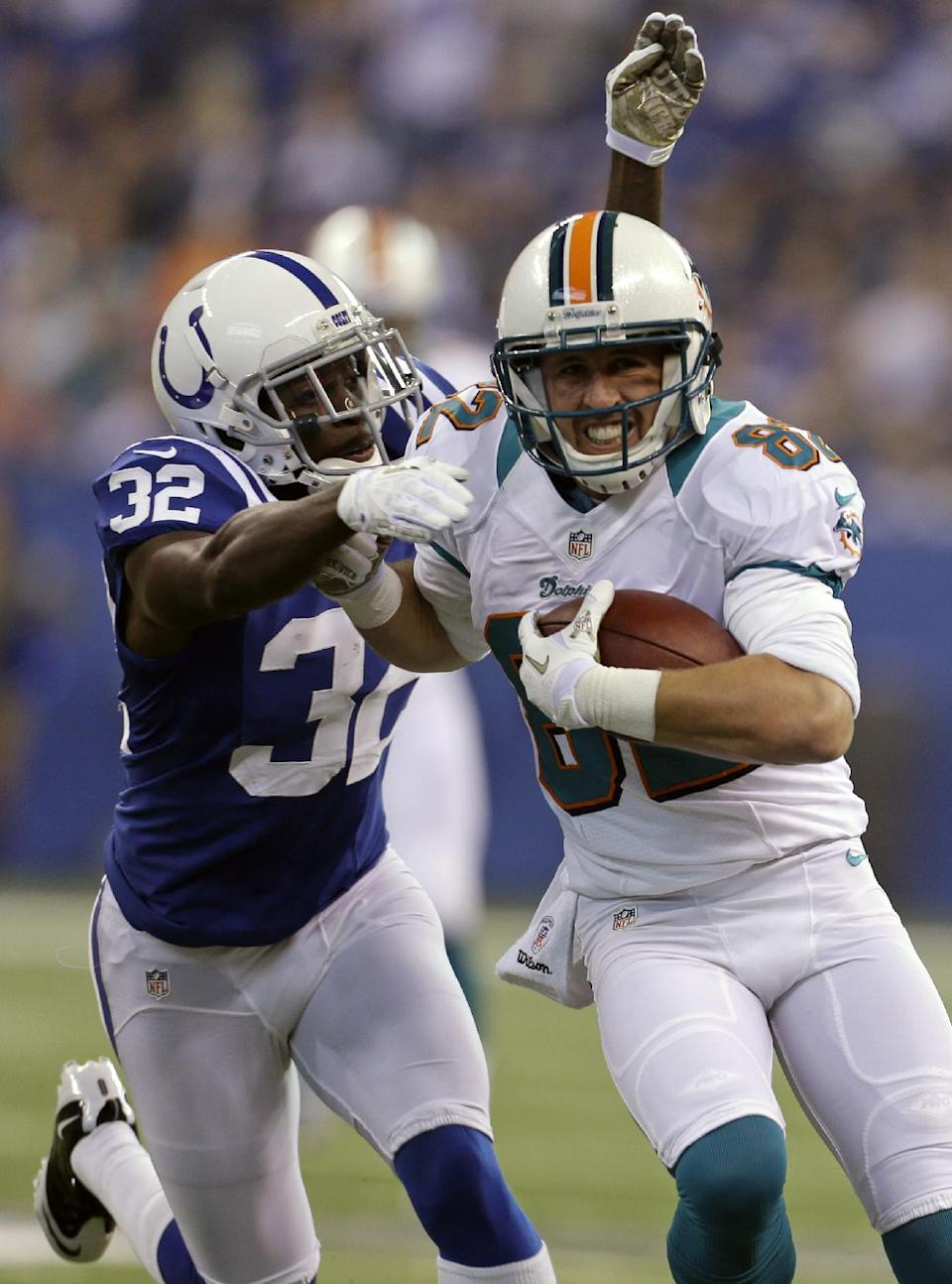 Miami Dolphins wide receiver Brian Hartline, right, tries to break the tackle of Indianapolis Colts cornerback Cassius Vaughn during the first half of an NFL football game in Indianapolis, Sunday, Nov. 4, 2012. (AP Photo/Darron Cummings)
