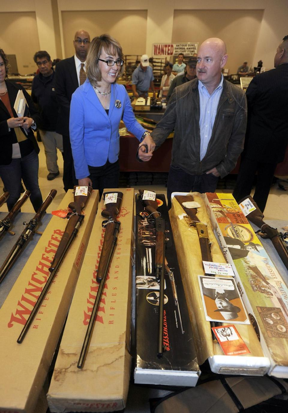 Former Arizona congresswoman Gabrielle Giffords, left, and her husband Mark Kelly tour the New EastCoast Arms Collectors Associates arms fair in Saratoga Springs, N.Y. on Sunday, Oct. 13, 2013. (AP Photo/Tim Roske, Pool)
