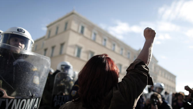 A Greek municipal employee confronts riot police after a group of protesters pushed into the grounds of Parliament during a protest in Athens Wednesday, Dec. 12, 2012. Riot police prevented the protesters from advancing much further, and there were no clashes or arrests. Municipal employees are angry at government plans to include them on a list of state employees up for forced redundancy under the country's austerity program. (AP Photo/Petros Giannakouris)