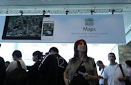 People walk under a poster for the new Maps application at the Apple 2012 World Wide Developers Conference in June 2012. Melting bridges, misplaced landmarks, and major cities disappearing: Apple's glitch-ridden maps program released in its new mobile software has customers fuming and analysts puzzled