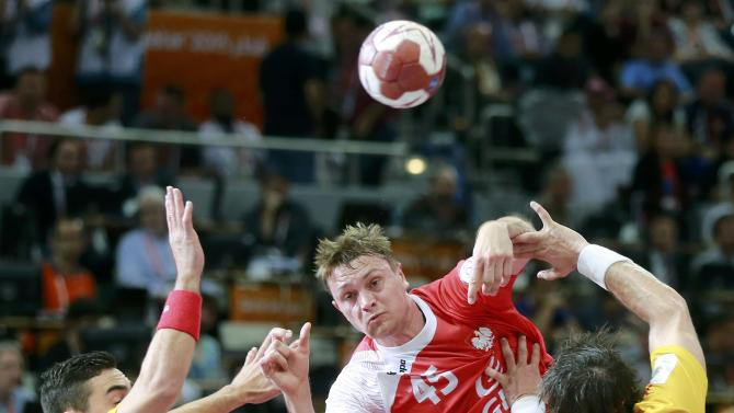 Szyba of Poland shoots between Rivera and Garcia of Spain during their third-place match of the 24th Men's Handball World Championship in Doha