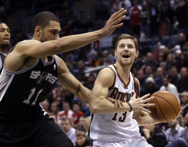 Milwaukee Bucks' Luke Ridnour(13) is fouled by San Antonio Spurs' Jeff Ayres(11) as he drives during the first half of an NBA basketball game Wednesday, Dec. 11, 2013, in Milwaukee