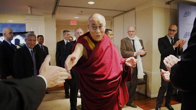 """Tibetan spiritual leader the Dalai Lama greets audience members as he arrives to speak at an event entitled: """"Happiness, Free Enterprise, and Human Flourishing"""" Thursday, Feb. 20, 2014, at the American Enterprise Institute in Washington. (AP Photo/Charles Dharapak)"""
