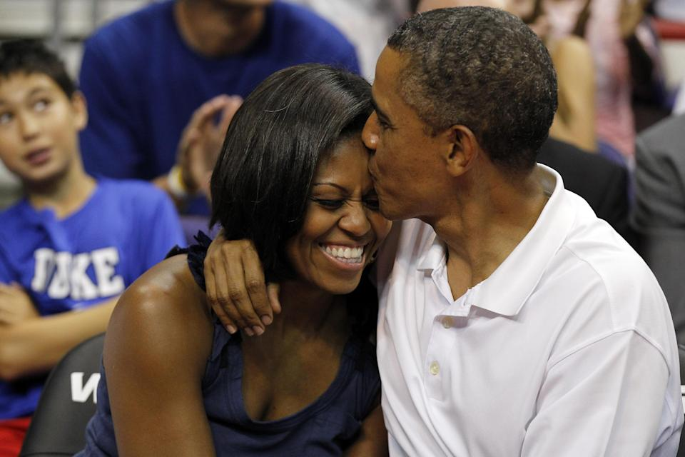 "President Barack Obama kisses the head of first lady Michelle Obama, left, after kissing her for ""Kiss Cam"" in the second half while attending the Olympic men's exhibition basketball game between Team USA and Brazil, Monday, July 16, 2012, in Washington. Team USA won 80-69. (AP Photo/Alex Brandon)"