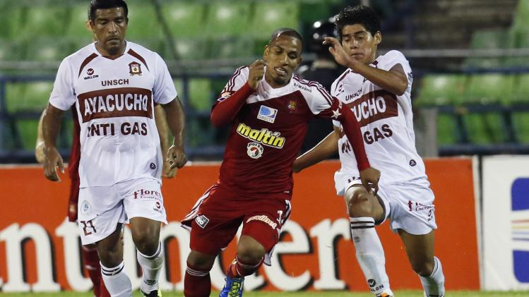 Peru's Inti Gas Brayan Arana challenges Venezuela's Caracas FC Romulo Otero during their Copa Sudamericana soccer match in Caracas