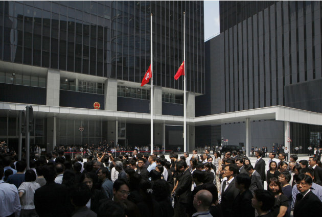 Hong Kong government officials pay tribute to victims who were killed in a ferry collision, with flying Chinese and Hong Kong flags at half-mast in the Central Government Office in Hong Kong Thursday,