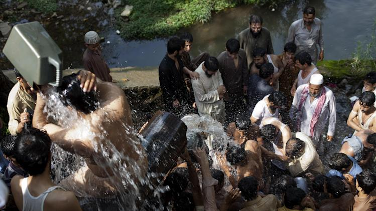 People cool themselves at a leaked water supply line in Islamabad, Pakistan, Friday, July 11, 2014, as temperature reached 38 degrees Celsius (100 Fahrenheit). Many cities in Pakistan are facing heat wave conditions with temperatures reaching up to 50 degrees Celsius (122 Fahrenheit) in some places. (AP Photo/B.K. Bangash)