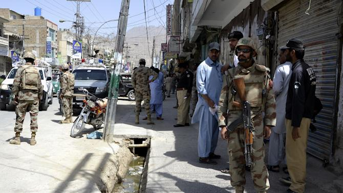 Pakistani security personnel gather after the killing of a shopkeeper by unidentified gunmen in Quetta, the capital of Baluchistan province, on May 25, 2015