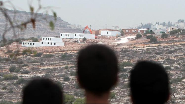 Palestinian children from the village of al-Mazraa al-Qabaliya look at bungalows in the distance built by Israeli settlers on seized land from the Palestinian village, near the West Bank city of Birzeit on December 3, 2013