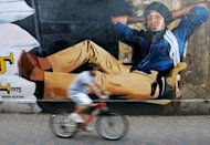 An Indian cyclist rides past a mural of Bollywood actor Amitabh Bachchan from his classic film 'Deewar'. Bachchan marked his 70th birthday with a lavish celebrity party and drawing hundreds of fans to cheer their hero outside his home
