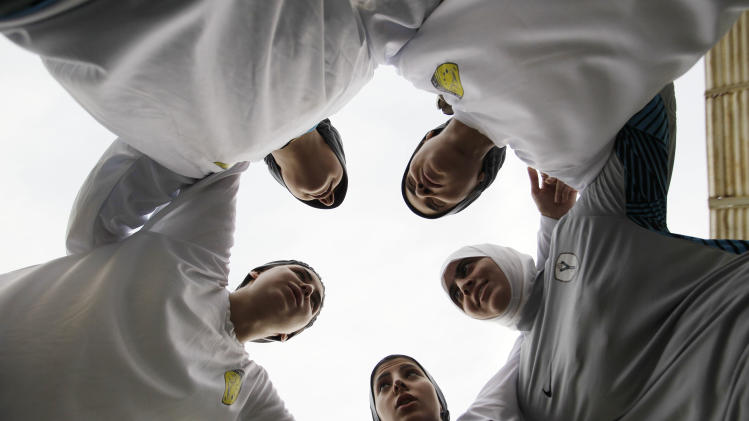In this May 21, 2012 photo, members of a Saudi female soccer team listen to their captain, Rawh Abdullah, bottom center, before their training session at a secret location in Riyadh, Saudi Arabia. While Olympic leaders and human rights advocates are encouraged by signs that Saudi Arabia may bow to pressure and send female athletes to the Summer Games, women athletes in the ultraconservative kingdom are worried about a backlash at home. (AP Photo/Hassan Ammar)