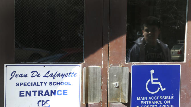 A young boy waits to enter the Lafayette Elementary School in Chicago on Thursday, March 21, 2013. At Lafayette, a school in the Humboldt Park neighborhood where 95 percent of its 483 students come from low-income families, the principal read teachers a letter from the district Thursday saying the school is among those it plans to close under a contentious plan that opponents say will disproportionately affect minority students in the nation's third largest school district. (AP Photo/Charles Rex Arbogast)