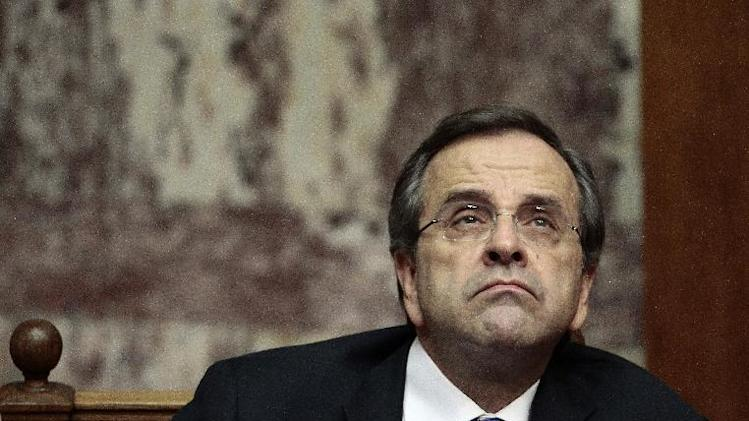 Conservative Prime Minister Antonis Samaras looks up during a debate in parliament late Sunday, Nov. 10, 2013. Samaras' 15-month-old coalition survived a vote of no-confidence called by the left wing opposition, but saw his support in parliament cut to 154 seats after a coalition lawmaker refused to back him. (AP Photo/Panagiotis Tzamaros/Fosphotos)