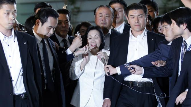 Japan's Justice Minister Midori Matsushima reacts as she is surrounded by reporters upon her arrival at PM Shinzo Abe's official residence for a meeting with Abe in Tokyo