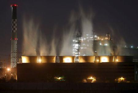 Smoke billows out from the cooling towers of a coal-fired power plant in Ahmedabad, India